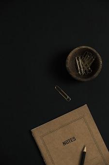 Feuille de cahier artisanal, papeterie sur fond noir.