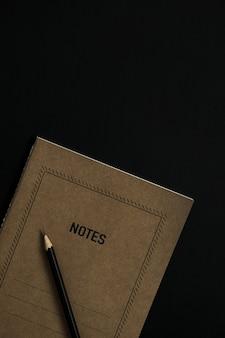 Feuille de cahier d'artisanat, crayon, clips sur noir