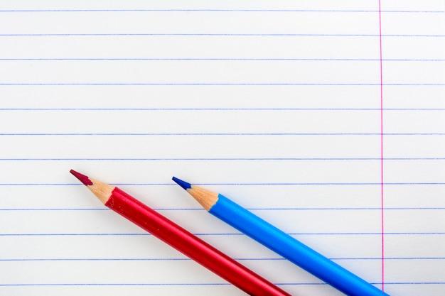 Feuille d'un cahier d'école dans la fourchette. deux crayons sur la feuille. crayons rouges et bleus.