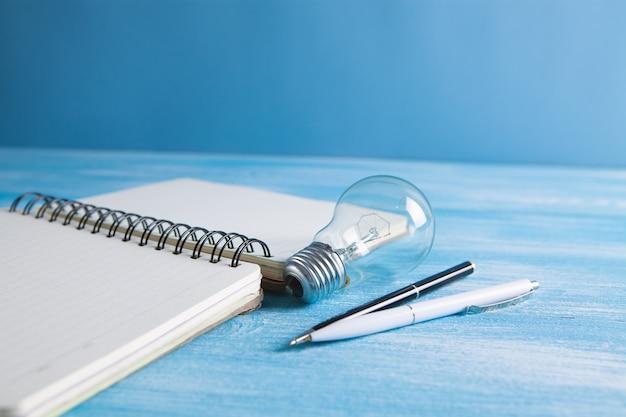 Feuille avec un cahier avec des stylos et une ampoule sur la table lk. nouvelles idées