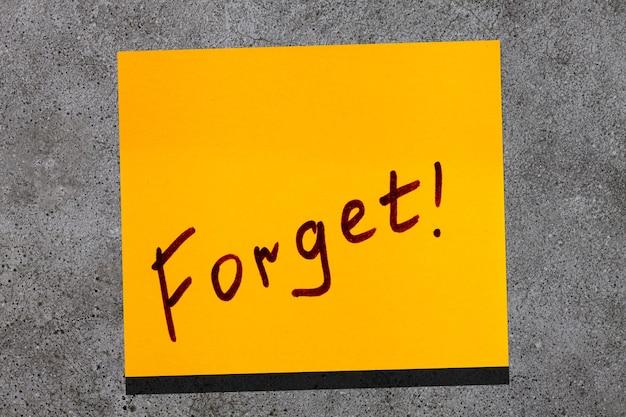 Feuille collante jaune sur le mur. marqueur d'inscription mot oublier