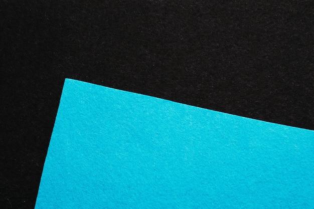 Feuille coudée de texture feutre bleu ciel sur collage géométrique minimaliste abstrait sombre