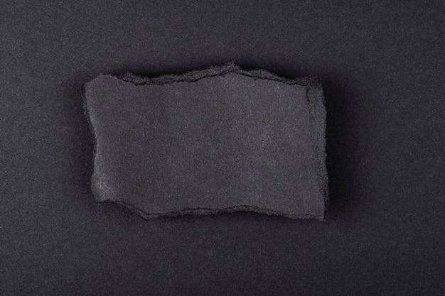 Feuille déchirée de papier noir sur fond noir.