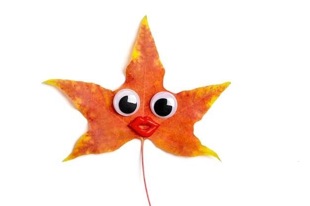 Feuille d'érable de couleur orange, jaune, rouge d'automne avec des yeux écarquillés et des lèvres drôles isolés sur blanc