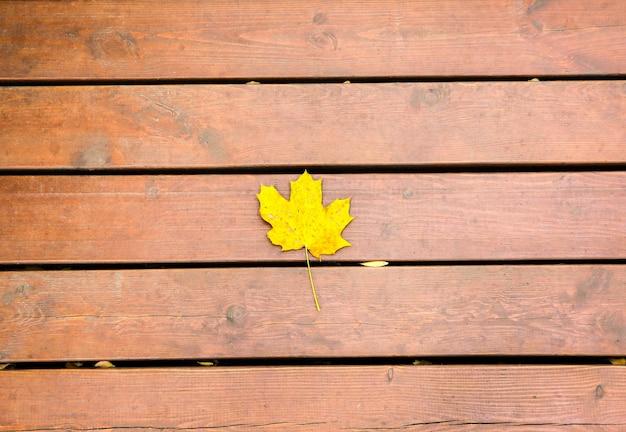Feuille jaune allongée sur le fond en bois. photo d'automne. textures naturelles.