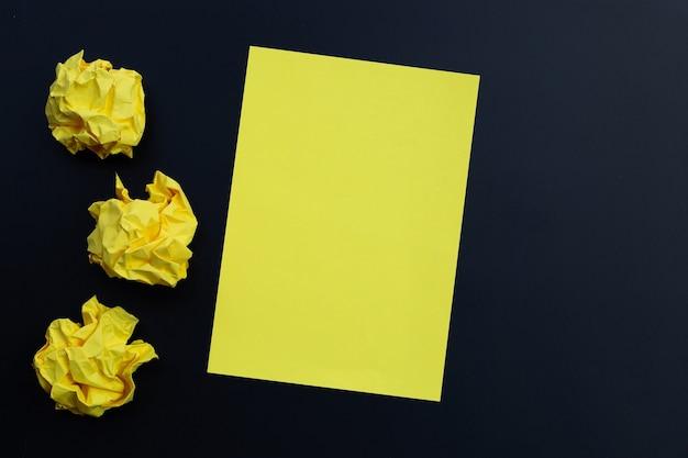 Feuille jaune avec des boules de papier froissé sur une surface sombre. copier l'espace