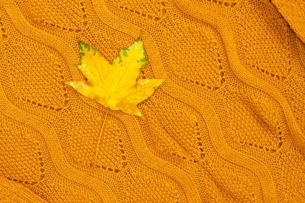 Une feuille jaune vif se trouve sur le pull. composition d'automne. filmé d'en haut.