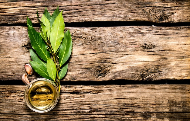 Feuille de laurier, ail et huile d'olive. sur fond en bois.