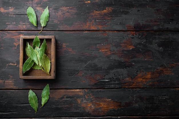 Feuille de laurier vert et frais, dans une boîte en bois, sur la vieille table en bois sombre