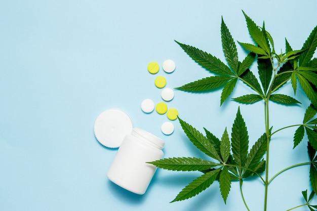 Feuille de marijuana avec des pilules médicales sur bleu.
