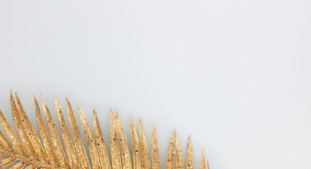 Feuille d'or de palmier sur fond bleu.