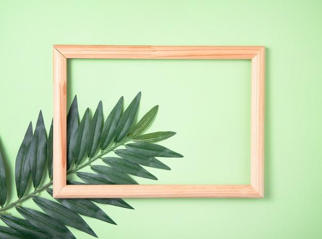 Feuille de palmier et cadre en bois sur fond vert. vue de dessus