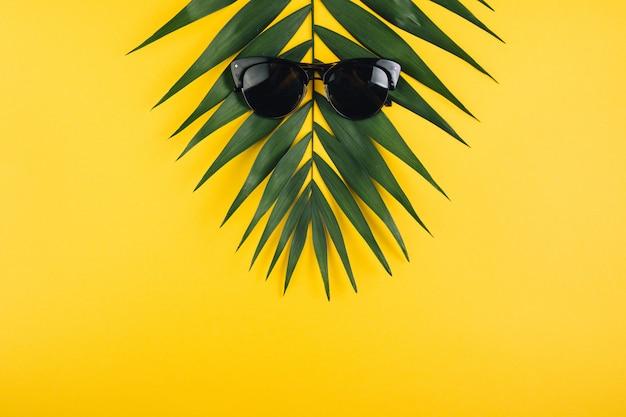 Feuille de palmier d'été tropical à lunettes de soleil. lay plat. concept minimal