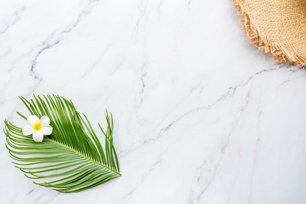 Feuille de palmier tropical, grand chapeau de paille, fleur sur marbre blanc
