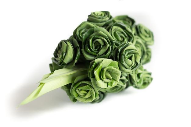 Feuille de pandanus frais tisser au bouquet de rose isolé sur blanc