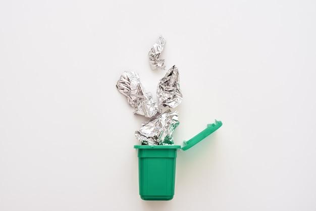 Feuille de papier d'aluminium froissé tombant dans le bac de recyclage