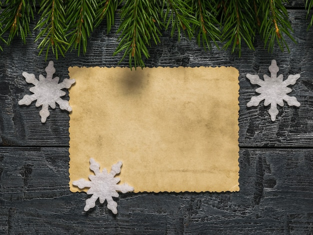 Une feuille de papier ancien avec des flocons de neige en papier et des branches de sapin sur une table en bois