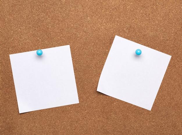 Feuille de papier blanc carré blanc attaché avec bouton bleu sur fond marron, espace copie