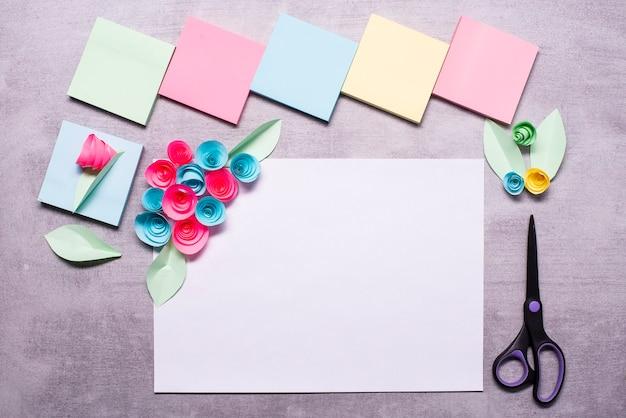 Feuille de papier blanc avec des fleurs en papier fabriquées à partir d'autocollants colorés