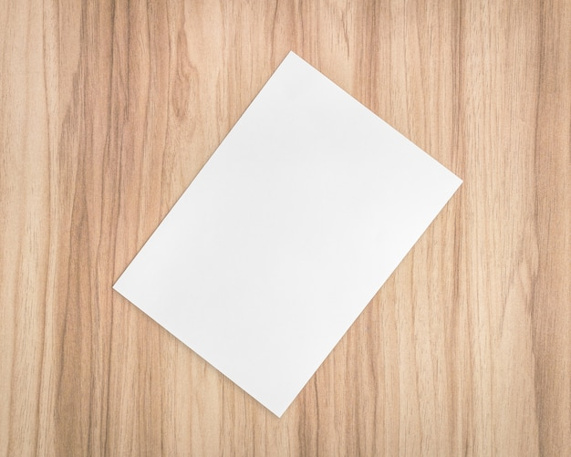Feuille de papier blanc sur fond en bois. modèle de document a4 et espace vide pour le texte.