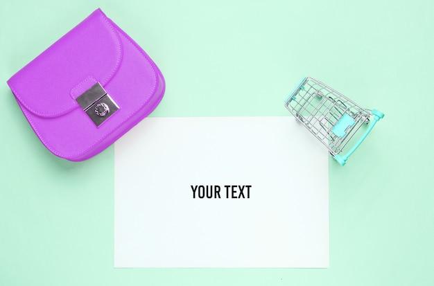 Feuille de papier blanc pour espace copie, mini caddie, sac sur fond bleu. fond de magasinage créatif