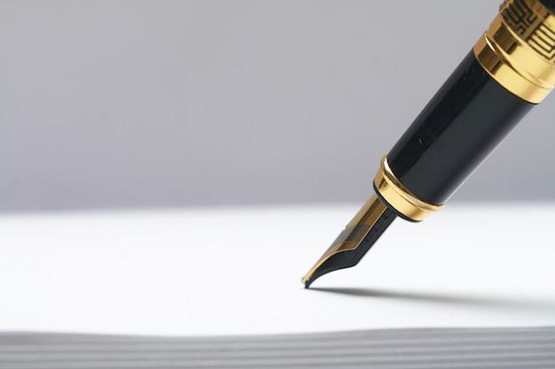 Une feuille de papier blanc et un stylo plume