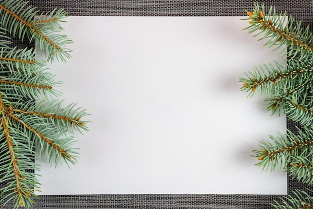 Une feuille de papier blanche décorée de branches d'un arbre de noël sur fond de nouvel an avec un espace sopi.