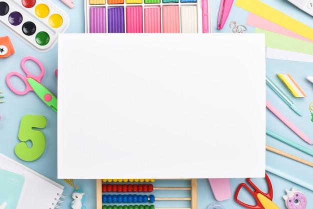 Une feuille de papier blanche sur le fond de la papeterie. retour à l'école. disposition plate, vue de dessus, un endroit pour copier.