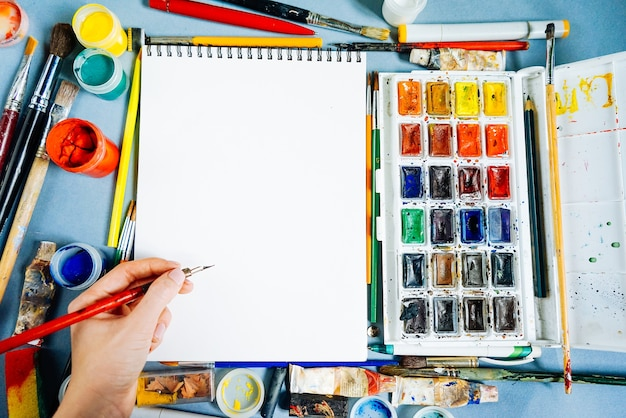 Feuille de papier blanche sur fond de peintures et de pinceaux multicolores