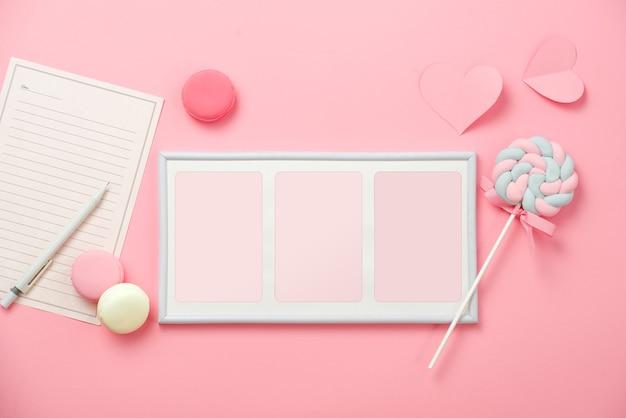Une feuille de papier blanche pour un message à un être cher, des bonbons avec cadre photo sur fond rose. concept de la journée de la femme heureuse. maquette