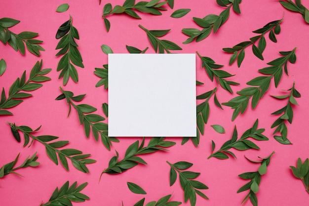 Feuille de papier carré blanc sur fond rose avec des feuilles
