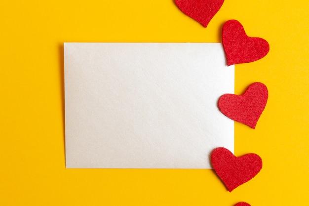 Feuille de papier avec des coeurs rouges pour message sur fond jaune
