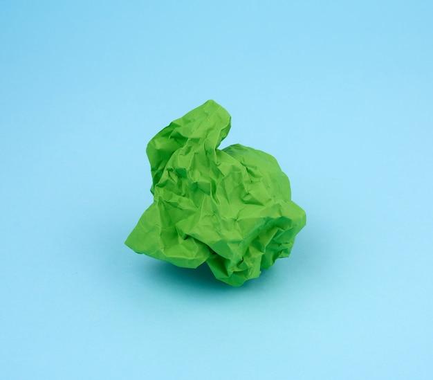 Feuille de papier froissé vert sur fond bleu