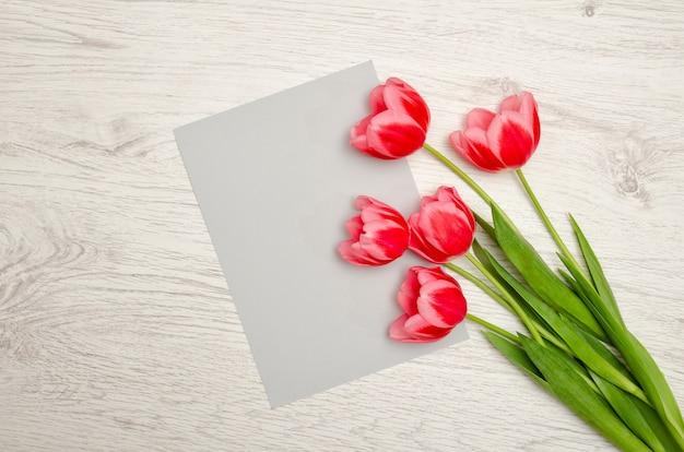 Feuille de papier grise et tulipes roses sur une table en bois clair