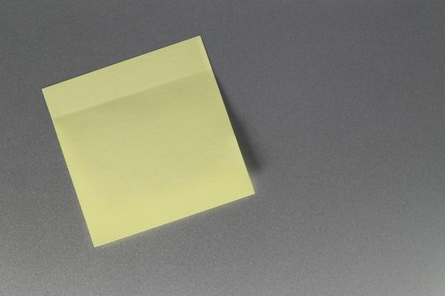 Feuille de papier jaune vide sur la porte du réfrigérateur pour la conception.