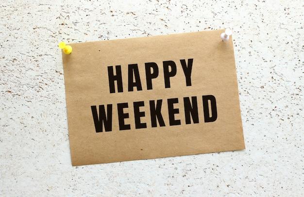 Une feuille de papier kraft avec du texte happy weekend attachée à un mur texturé blanc avec un bouton. rappel de bureau.