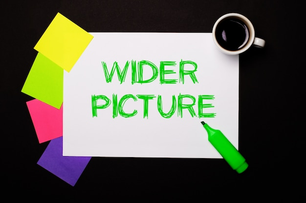 Une feuille de papier avec les mots wider picture, une tasse de café, des autocollants multicolores lumineux pour les notes et un marqueur vert