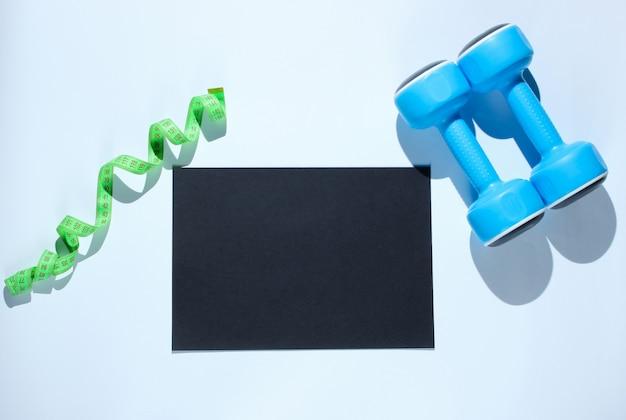 Feuille de papier noire pour l'espace de copie, haltères en plastique, règle sur table grise. table de fitness créative