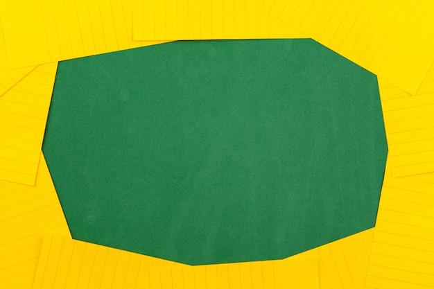 Une feuille de papier orange se trouve sur un tableau d'école vert constituant un cadre pour le texte. espace copie plat lay vue de dessus concept education.