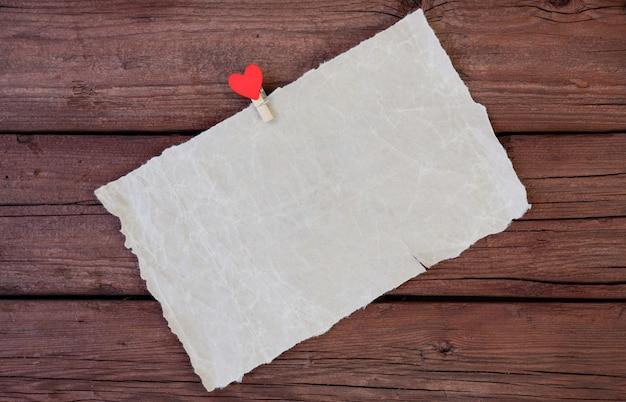 Une feuille de papier parchemin avec une pince à linge avec un coeur rouge sur un fond en bois. copiez l'espace