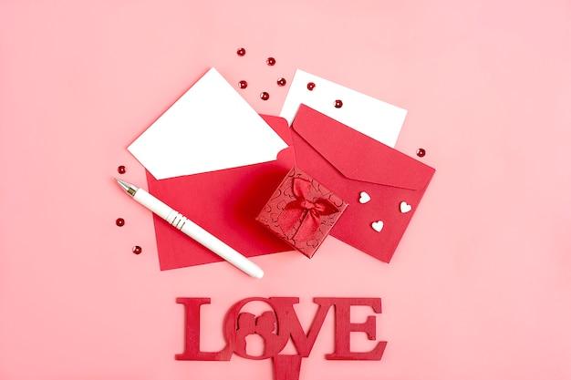 Feuille de papier pour le message, enveloppe rouge, boîte-cadeau, étincelles, crayon bonne fête de la saint-valentin