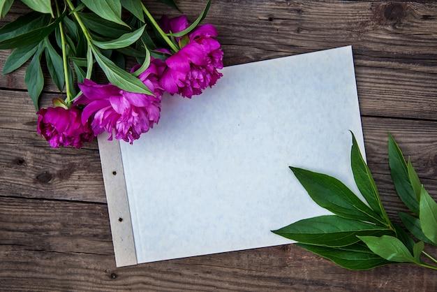 Une feuille de papier et quelques pivoines roses sur fond de bois avec copie espace comme carte postale