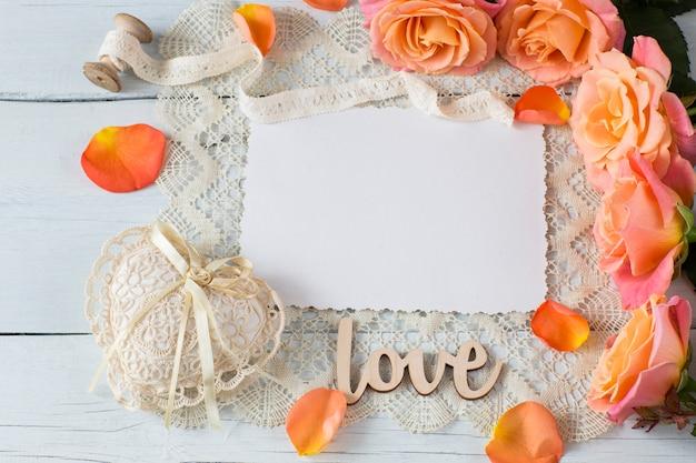 Une feuille de papier, des roses orange, un coeur de dentelle, des pétales de rose et de la dentelle