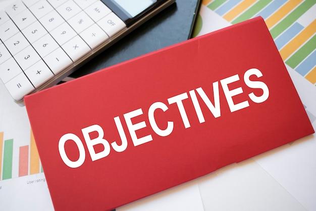 Feuille de papier rouge avec les objectifs de texte, la calculatrice et le stylo sur le bureau. concept d'entreprise