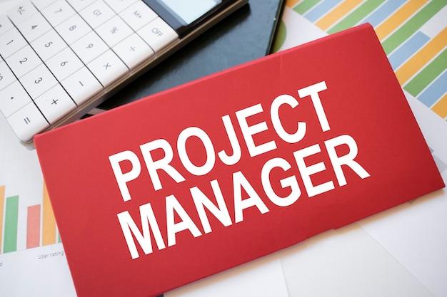 Feuille de papier rouge avec le texte project manager, calculatrice et stylo sur le bureau. concept d'entreprise