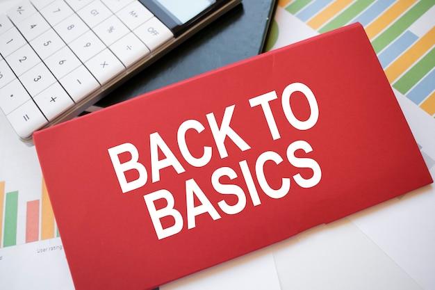 Feuille de papier rouge avec le texte de retour à l'essentiel, calculatrice et stylo sur le bureau. concept d'entreprise
