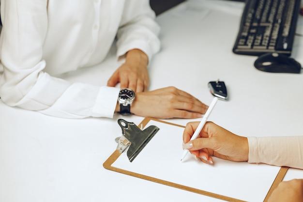 Feuille de papier de signature de main féminine sur le presse-papiers