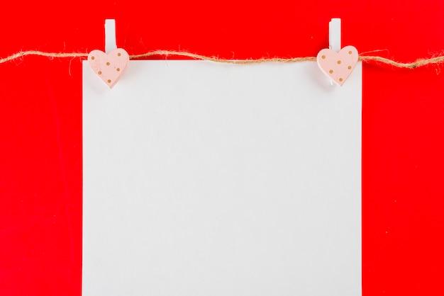 Feuille de papier suspendue à des piquets de coeur