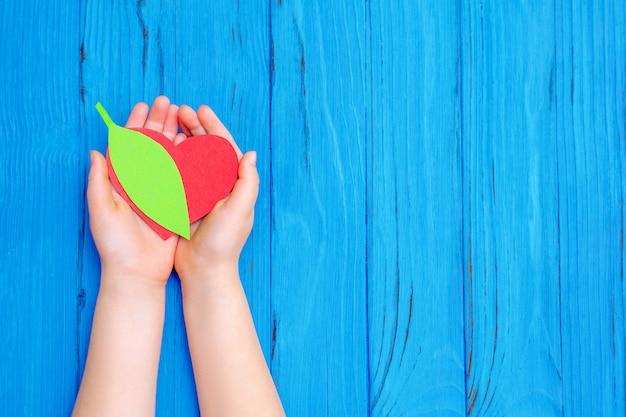Feuille de papier vert dans les mains de l'enfant