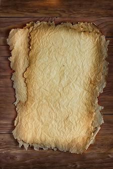 Feuille de papier verticale froissée sur une table en bois, fond grunge